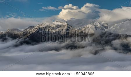 Snow mountain tops in clouds. Dawn. Greater Caucasus Mountain Range. Caucasus mountains. Karachay-Cherkessia. Russia.