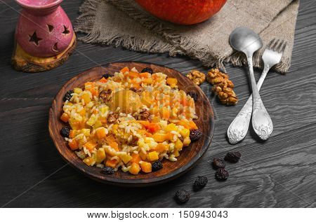 Pumpkin risotto with raisins. Rice porridge with sweet pumpkin raisins nuts apricot. Fresh pumpkin for Halloween rice. Sacking dark wood background.