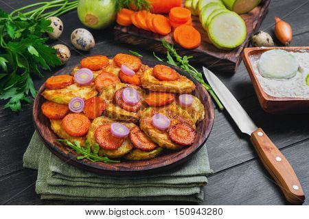 Vegetables ingredients for fried vegetable dishes in dough. Vegetables marrows white squashes carrots parsley lettuce dill tomato onions quail eggs flour Black wood background