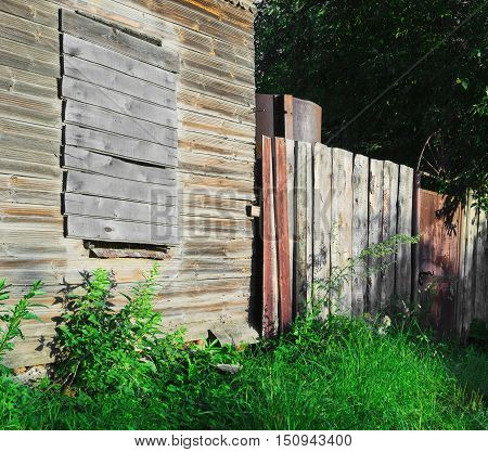Old brown-gray abandoned wooden country house with boarded up windows rickety fence green grass and trees metal gate summer