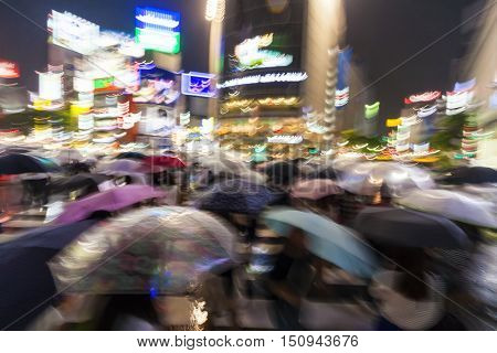 Motion blurred people with umbrellas in the rain at night on the Shibuya Crossing, Tokyo, Japan