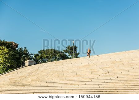 Washington D.C., USA - August 4, 2016: One fit man running on steps in shorts next to Lincoln memorial