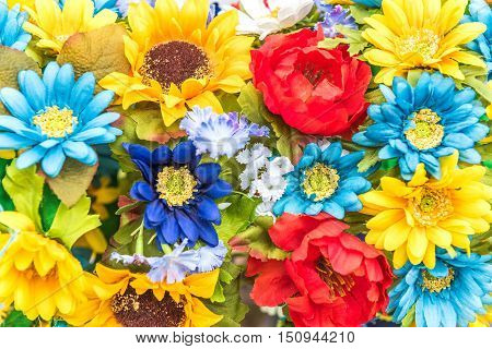 Closeup of Ukrainian colored blue and yellow fake cloth sunflowers