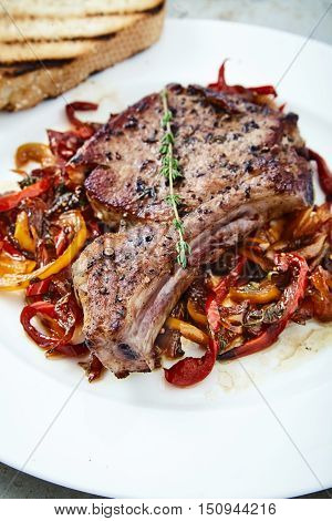 Delicious, juicy, fleshy, hot meat ribs on sauteed peppers and onions, decorated with a thyme sprig. Appetizing main dish on white plate with fried bun. Real mens food. Club Steak veal on the bone.