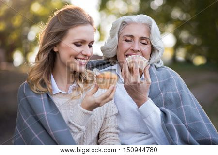 Every moment to enjoy. Happy charming mother and daughter smiling and eating cakes while sitting on the ground.