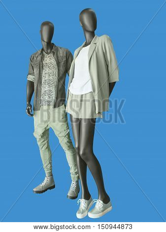 Two mannequins male and female dressed in casual clothes. Isolated on blue background. No brand names or copyright objects.