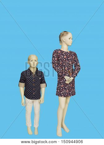 Two mannequins dressed in fashionable kids wear. Isolated on blue background. No brand names or copyright objects.
