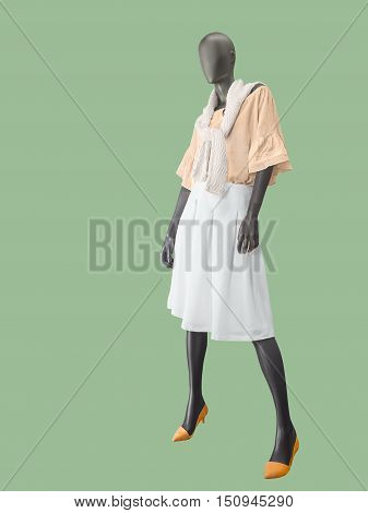 Full-length female mannequin dressed in white skirt and pink blouse. Isolated on green background. No brand names or copyright objects.
