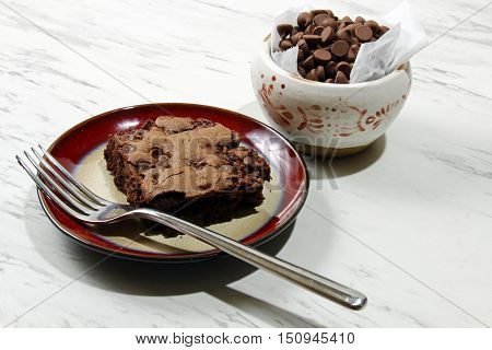 Chocolate brownies with chocolate chips on a plate with a bowl of chocolate chips selective focus.