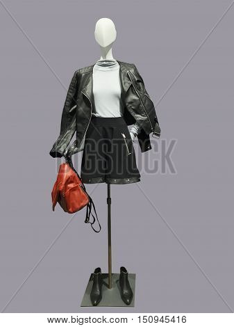 Female mannequin wearing leather jacket black skirt and sweater isolated. No brand names or copyright objects.