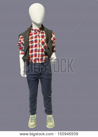 Child mannequin dressed in plaid shirt and jeans isolated on white background. No brand names or copyright objects.