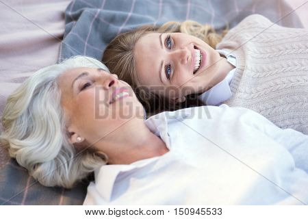 Our dreams will come true. Happy delighted mother and daughter smiling and talking while lying on the plaid.