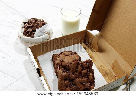 Chocolate brownies in a go to box with chocolate chips on a plate with a bowl of chocolate chips selective focus.