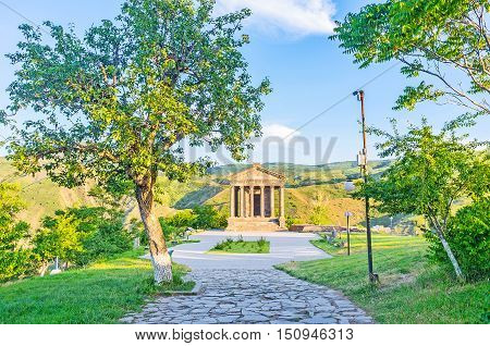 The shady path among the trees leads to the Garni Temple Kotayk Province Armenia.