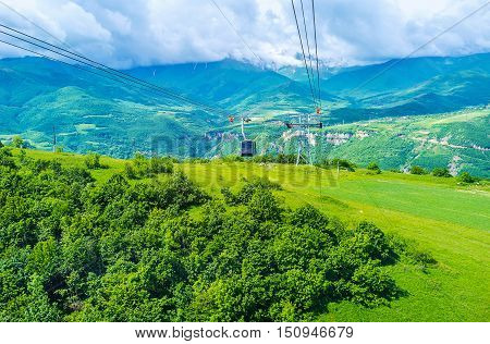 The cable car and tower of Wings of Tatev cableway riding over Halidzor agriculture lands and forests Syunik Province Armenia.