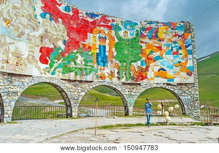 GUDAURI GEORGIA - JUNE 3 2016: The colorful Arch of Friendship of the Peoples located at the viewpoint on the Cross Pass on June 3 in Gudauri.