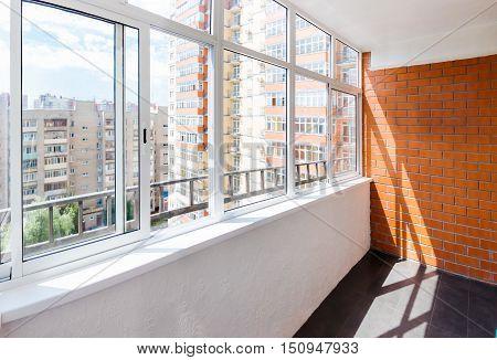 Empty glazed balcony with brick wall at sunny day