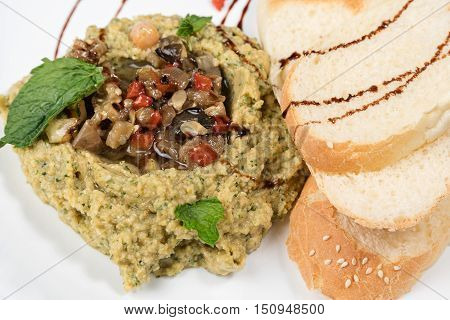Hummus with roasted vegetables served on a plate with bread and sauce