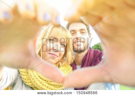 Best friends couple taking selfie with heart shape during a walk in the park. Boyfriend and girlfriend in love enjoying happy moments of life and spending time together. Main focus on girl face.