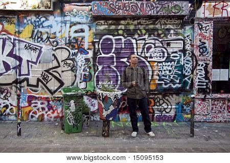 young man standing over graffiti wall