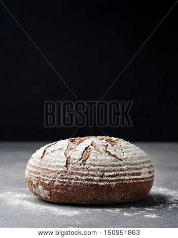 Rye, whole grain bread on a grey stone background. Copy space