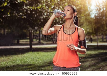 A sip of harmony. Young active delighted girl drinking water after doing her morning exercises and running in a park using headphones.