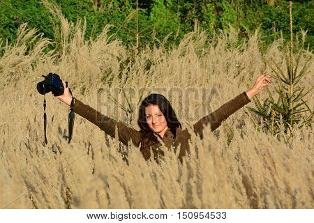 Young long haired brunette girl nature photographer in tall golden colored grass in the middle of autumn field looking cheerful after well done job