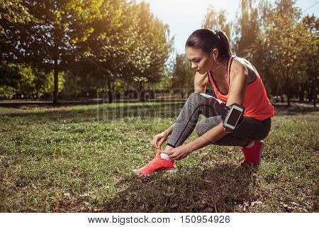 Be ready. Active young beautiful girl tying her shoelaces before doing morning exercises while listening to music with her headphones.