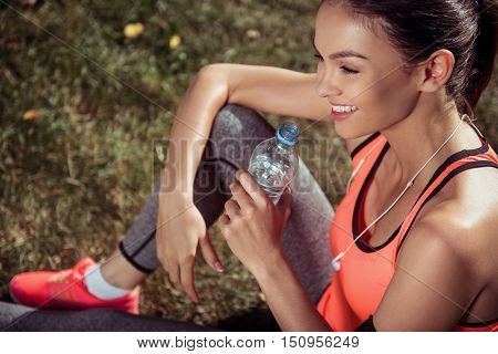 Thirsty but happy. Active young pretty girl having rest after doing morning exercises holding a bottle of water and wearing headphones.
