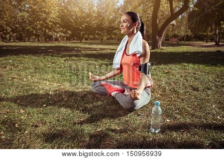 Yoga brings harmony. Young inspired beautiful girl sitting in lotus posture after having morning exercises and wearing towel and smartphone holder.