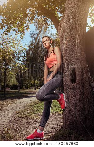 Enjoy the nature. Smiling young beautiful girl enjoying the nature and standing behind the tree after doing morning exercises.