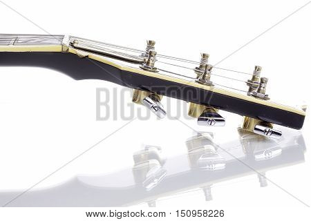 Headstock of an electric rock guitar (complete with cigarette burn) isolated against a white background with reflection.