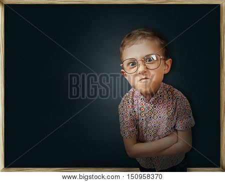 Emotional pupil boy near the school chalkboard .