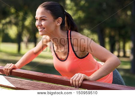 Improve your body. Active young athletic girl doing pushups while training and enjoying sunlight in the park.