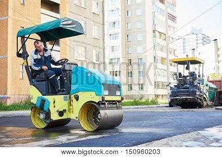 Road construction. Worker on steam vibration roller compacting asphalt