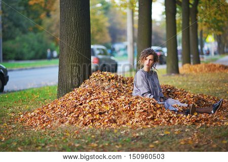Young modern girl sitting near a tree on a pile of autumn leaves next to on a city street going cars.