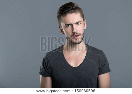 Puzzled feelings. Confused bearded young man opening his mouth while standing isolated in grey background