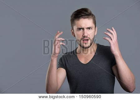 Shock. Puzzled bearded young man opening his mouth and raising his hands while standing isolated in grey background