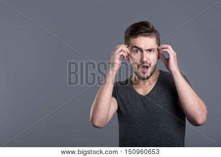 Huge shock. Shocked bearded young man opening his mouth and raising his hands while standing isolated in grey background