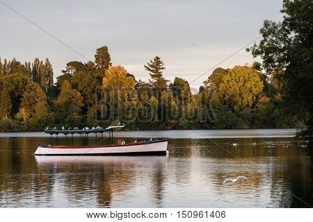 Old wooden pleasure boat moored on the mere at Ellesmere Shropshire in England at sunset