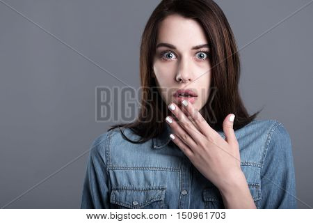 Phobias are close. Scared young woman raising her hand and opening mouth while standing against grey background