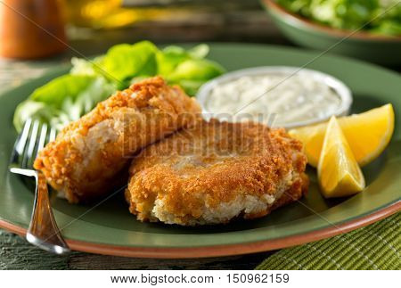 A plate of delicious homemade fishcakes with lemons green salad and tartar sauce.