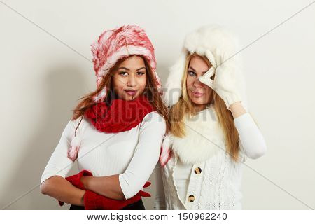 Fashion winter people concept. Two girls with winter outfit. Attractive women wearing fur caps.