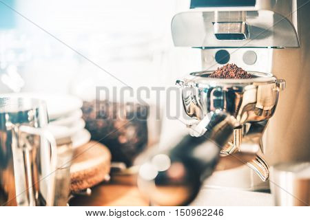 Espresso Coffee Grinding in Professional Coffee Grinder. Portafilter Loaded with Freshly Grinded Coffee.