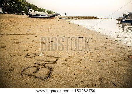 Bali Indonesia written in sand at Sanur Beach sunset