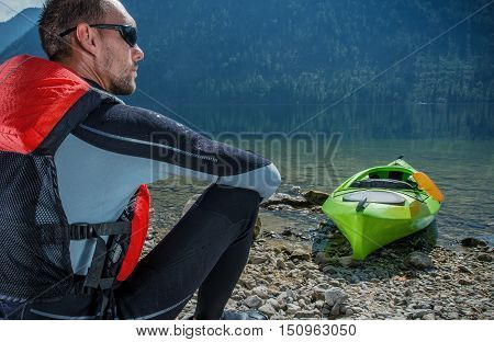 Kayaker and the Lake. Caucasian Kayaker in His 30s Resting on the Lake Shore After Long Kayak Trip.