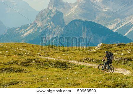 Mountain Biking Adventures. Men on the Bike on the Mountain Trail. Italian Dolomites.