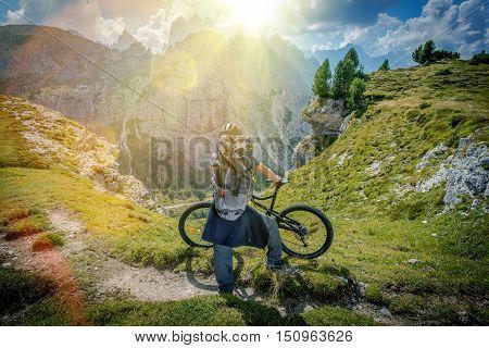 Mountain Trail Biking. Scenic Place in the Mountains. Caucasian Biker Taking Moment to Enjoy the View. Italian Dolomites.