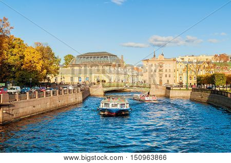 ST PETERSBURG RUSSIA-OCTOBER 3 2016. Moika river - historic buildings and touristic boat floating to First Engineer Bridge in sunny day in St Petersburg Russia. City view of St Petersburg Russia
