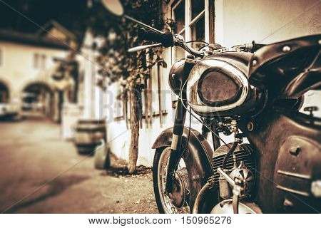 Vintage Motorcycle Closeup. Parked Aged Motorcycle in the Small European Village.